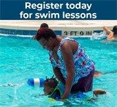 Women helping child swim in pool