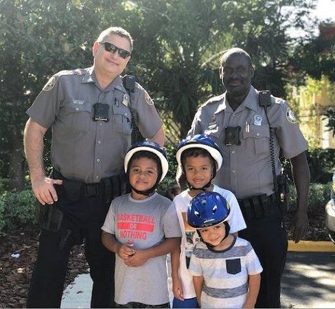 photo of police and children giving bike helmets